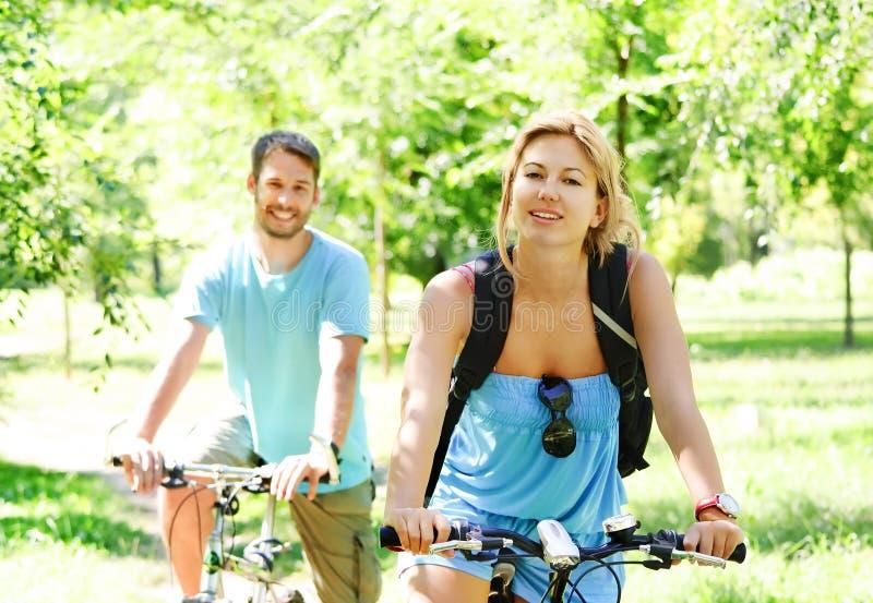 Pares felizes novos que montam uma bicicleta imagens de stock royalty free