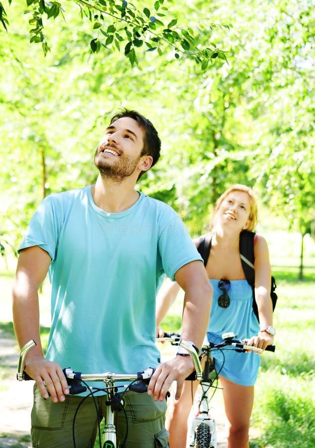 Pares felizes novos que montam uma bicicleta fotografia de stock royalty free