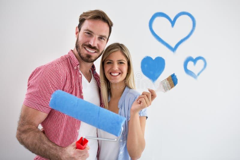 Pares felizes novos que pintam o apartamento novo fotos de stock royalty free