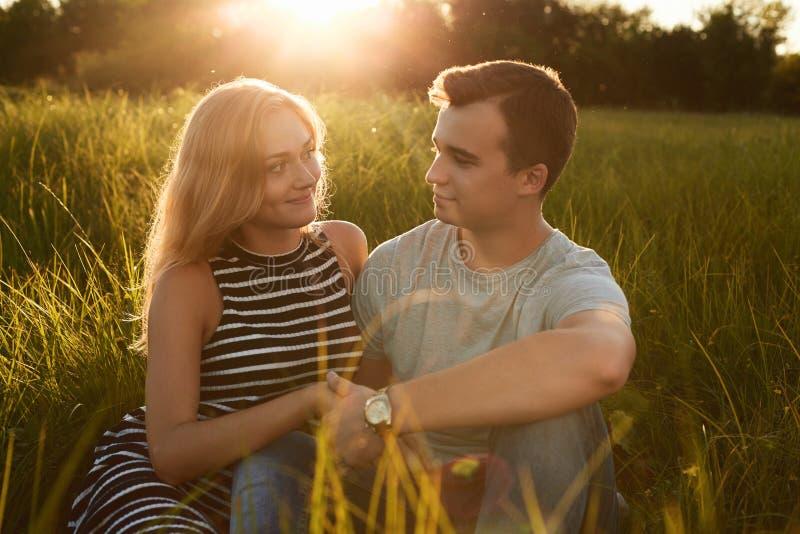 Pares felizes novos que sentam-se junto na grama que guarda suas mãos fotografia de stock
