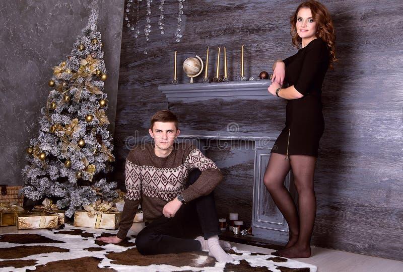 Pares felizes novos que sentam-se na frente da árvore de Natal imagens de stock royalty free