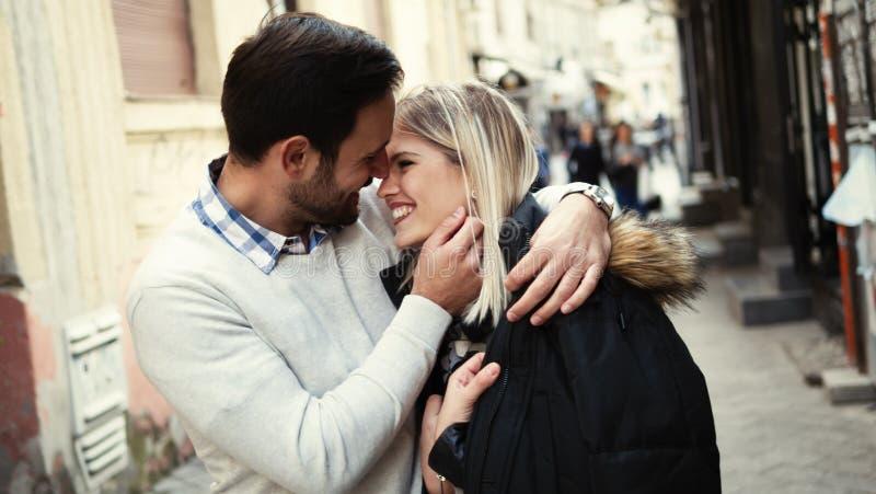 Pares felizes novos românticos que beijam e que abraçam foto de stock