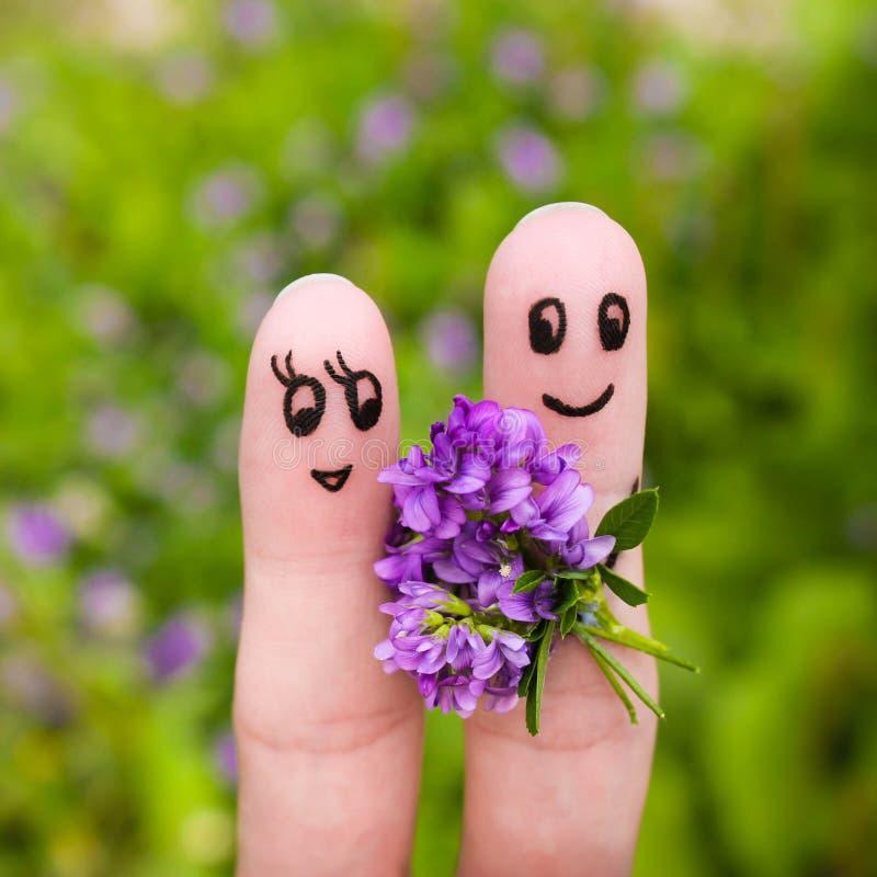 Pares felizes O homem está dando flores a uma mulher fotografia de stock royalty free