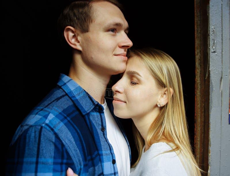 Pares felizes que abraçam, close-up, louro suporte em um abraço preto do fundo fotografia de stock