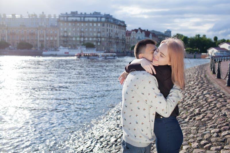 Pares felizes que abraçam e que riem junto na praia imagens de stock