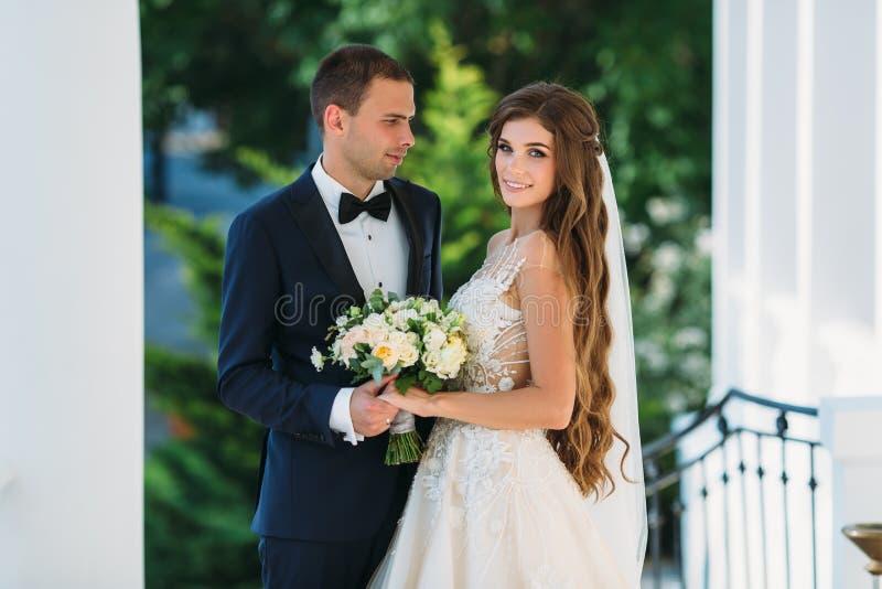 Pares felizes que abraçam e que sorriem no jardim com árvores verdes A noiva em um terno preto com um laço e uma noiva na foto de stock royalty free