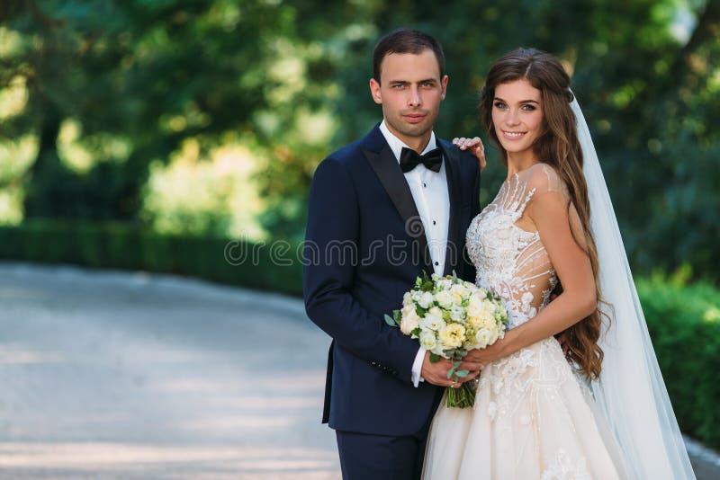 Pares felizes que abraçam e que sorriem no jardim com árvores verdes A noiva em um terno preto com um laço e uma noiva na foto de stock