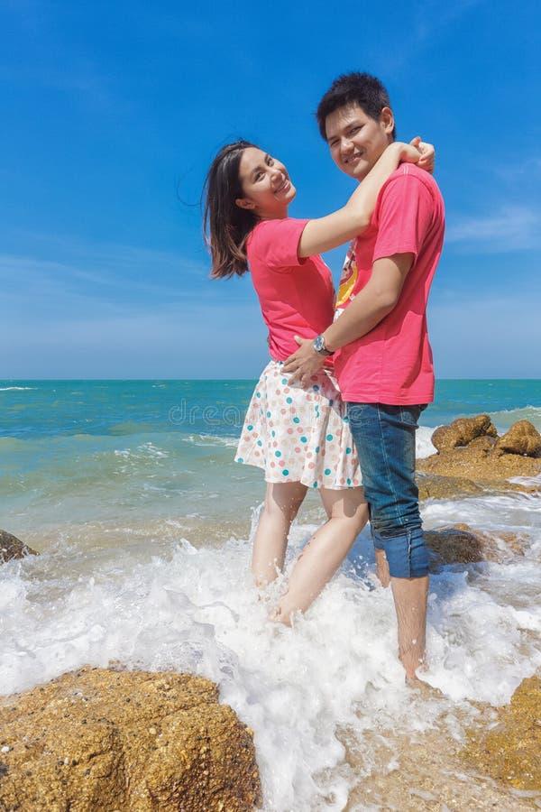 Pares felizes que abraçam junto na praia imagem de stock