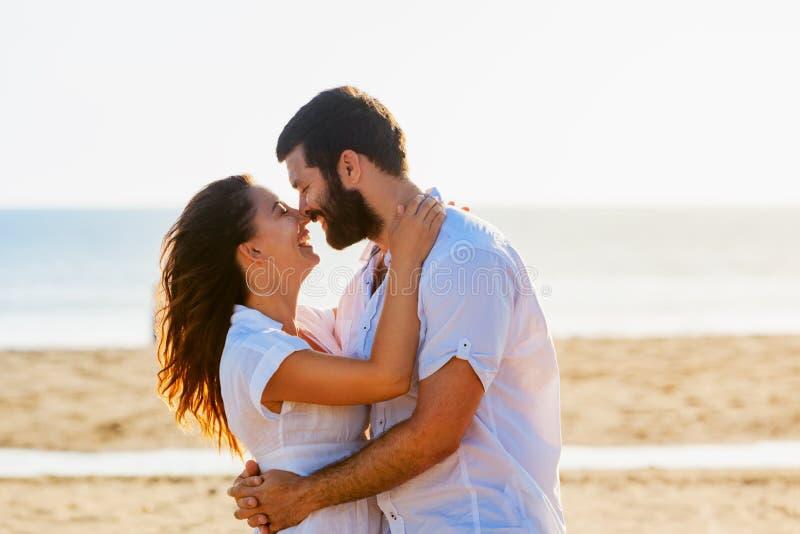 Pares felizes que abraçam na praia do mar foto de stock