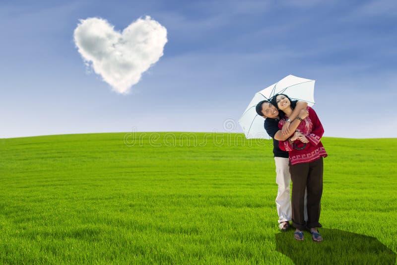 Pares felizes que abraçam sob a nuvem do amor imagens de stock royalty free