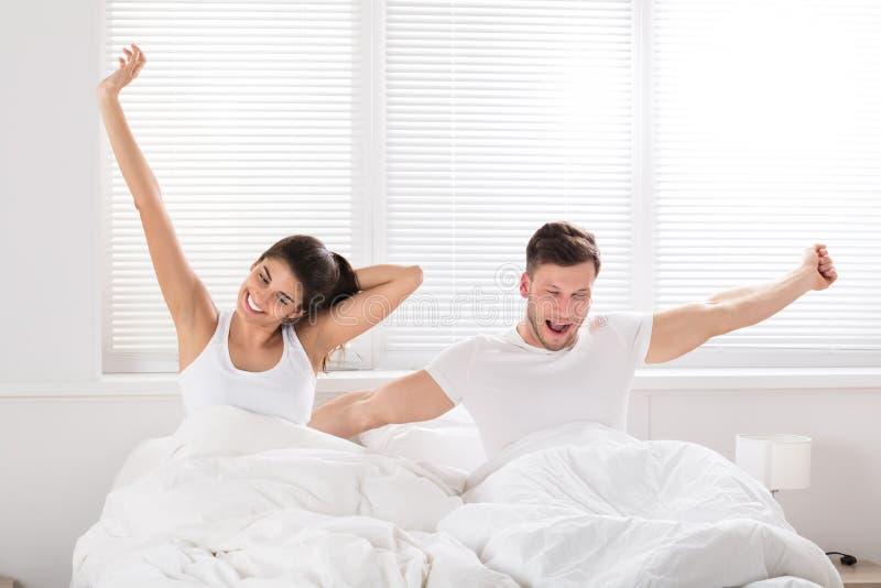 Pares felizes que acordam na cama fotografia de stock royalty free