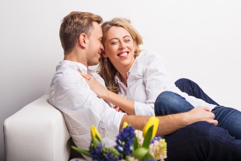 Pares felizes que afagam no sofá imagens de stock royalty free