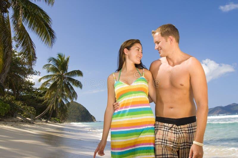 Pares felizes que andam ao longo de uma praia tropical imagem de stock royalty free