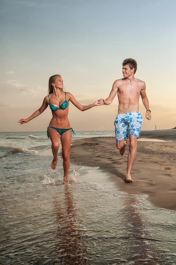 Pares felizes que apreciam férias na praia fotos de stock