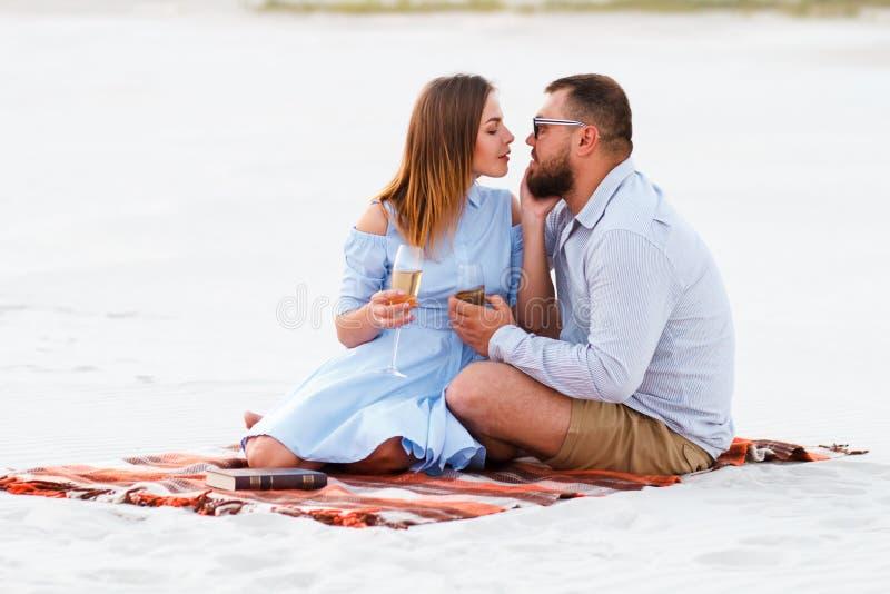 Pares felizes que apreciam o piquenique na praia branca da areia e que bebem vinho ou o champanhe durante o jantar romântico, par fotografia de stock