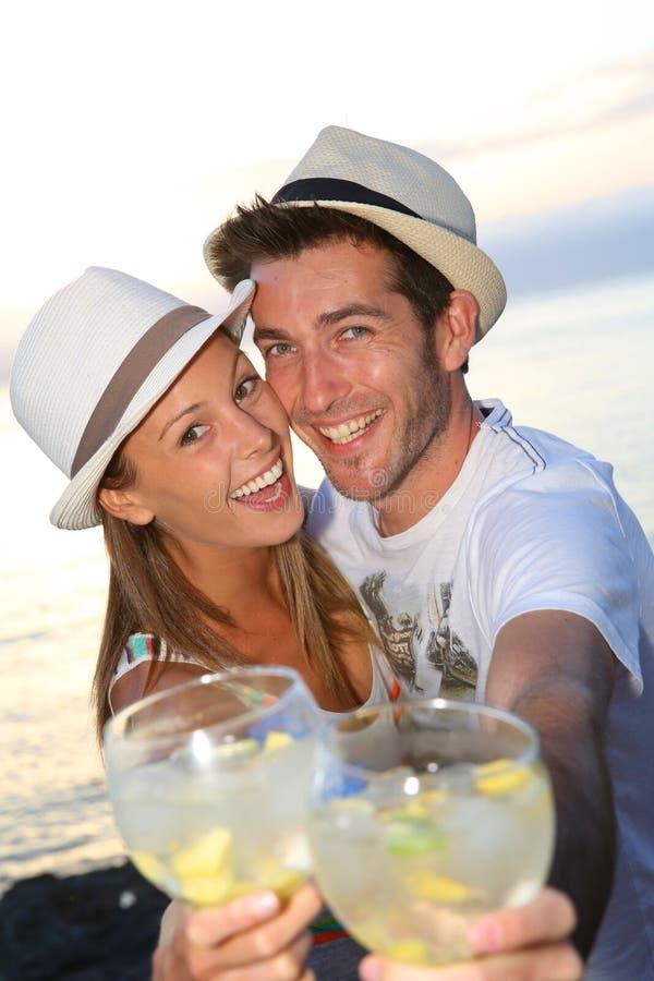 Pares felizes que apreciam os feriados que bebem cocktail foto de stock royalty free