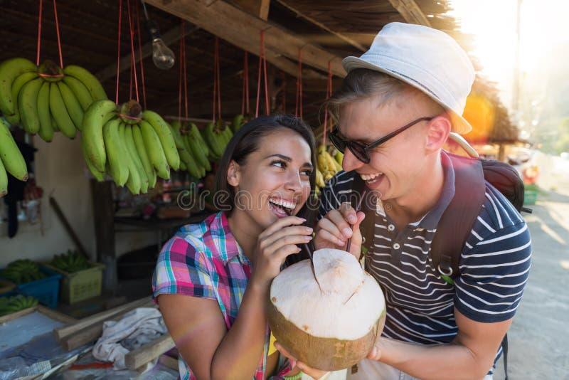 Pares felizes que bebem um coco no mercado de rua de Tailândia, em turistas alegres homem e em jovens da mulher em frutos tradici fotografia de stock royalty free