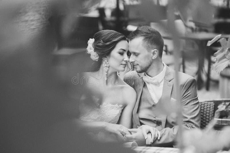 Pares felizes que beijam ao sentar-se no café da rua imagens de stock royalty free