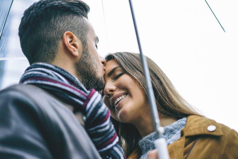 Pares felizes que beijam sob um guarda-chuva em um dia chuvoso - homem considerável para beijar sua amiga da testa sob a chuva -  imagens de stock royalty free