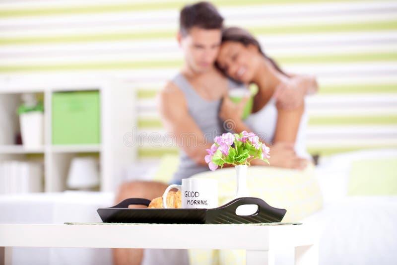 Pares felizes que comem o café da manhã na cama fotografia de stock royalty free