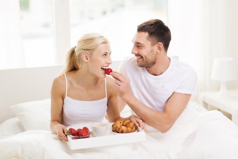 Pares felizes que comem o café da manhã na cama em casa imagem de stock royalty free