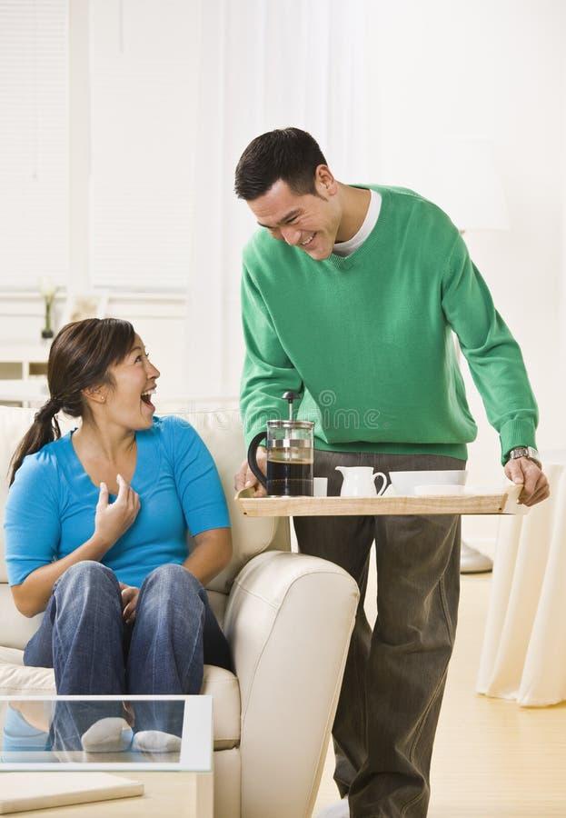 Pares felizes que comem o café em casa fotografia de stock royalty free