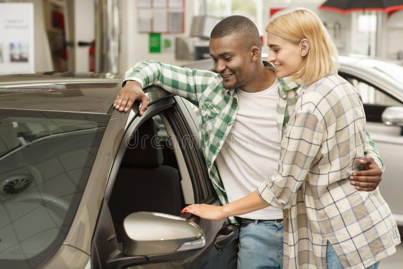 Pares felizes que compram o carro novo junto no negócio fotografia de stock