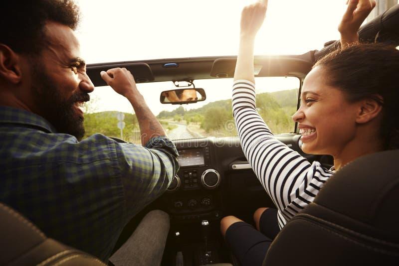Pares felizes que conduzem em seu carro com os braços no ar imagens de stock