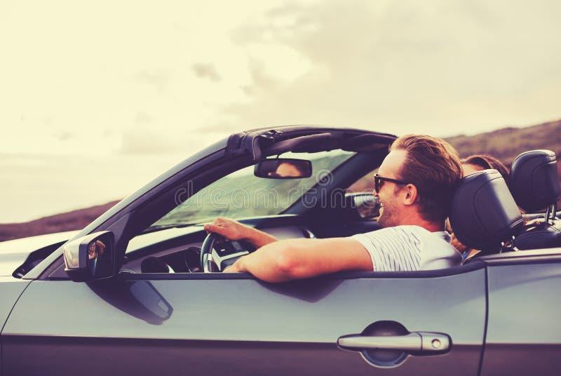 Pares felizes que conduzem no Convertible imagens de stock