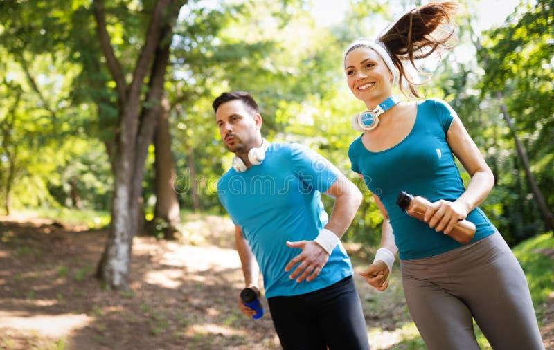 Pares felizes que correm e que exercitam junto exterior fotografia de stock royalty free