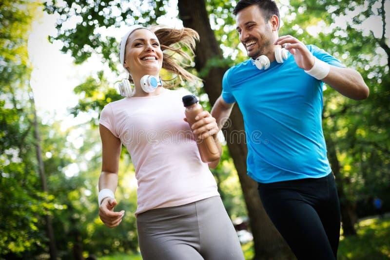 Pares felizes que correm e que exercitam junto exterior foto de stock royalty free