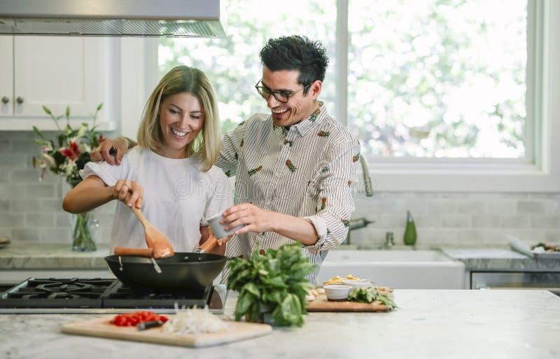 Pares felizes que cozinham na cozinha foto de stock