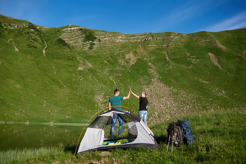 Pares felizes que dão altamente cinco perto do acampamento contra na montanha verde poderosa foto de stock