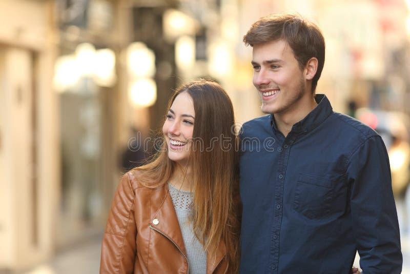 Pares felizes que datam o passeio na rua que olha o lado fotografia de stock royalty free