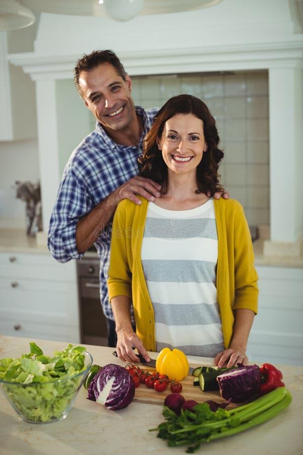 Pares felizes que desbastam vegetais na cozinha fotos de stock