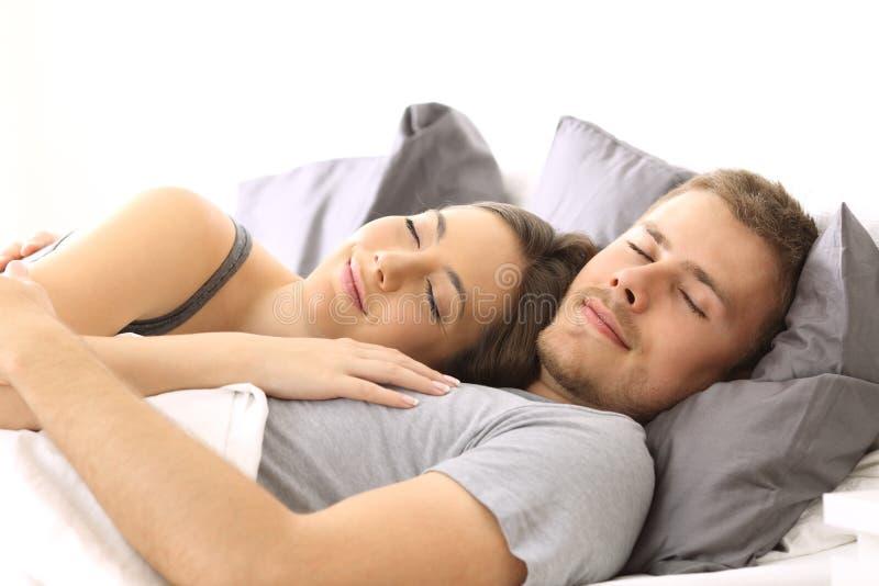 Pares felizes que dormem junto em uma cama imagem de stock