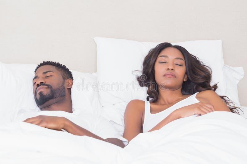 Pares felizes que dormem na cama junto imagens de stock royalty free