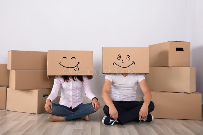 Pares felizes que encontram-se em caixas de cartão vestindo do assoalho fotos de stock