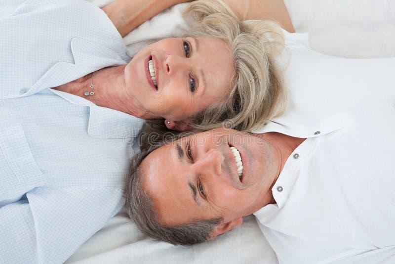Pares felizes que encontram-se na cama foto de stock royalty free