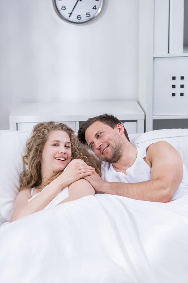 Pares felizes que encontram-se na cama fotos de stock