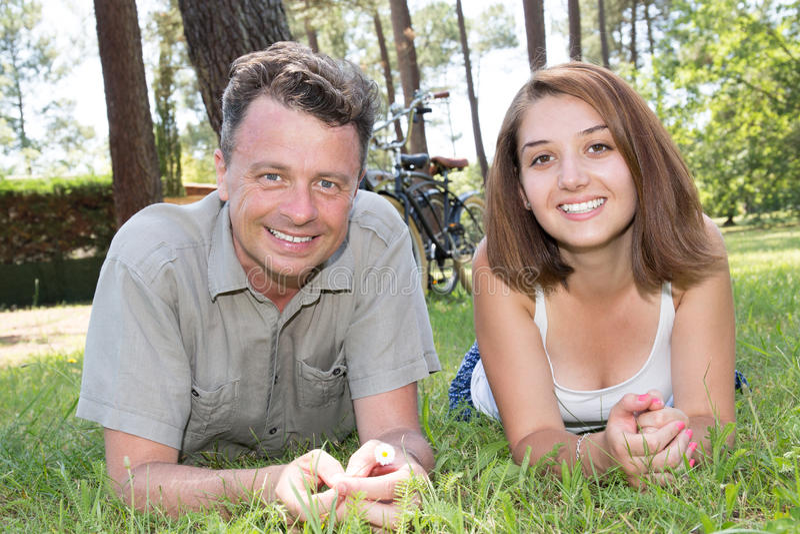 Pares felizes que encontram-se na grama no jardim Resto dos amantes fotos de stock royalty free