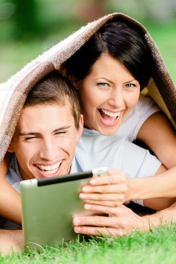 Pares felizes que encontram-se na grama verde com almofada imagem de stock