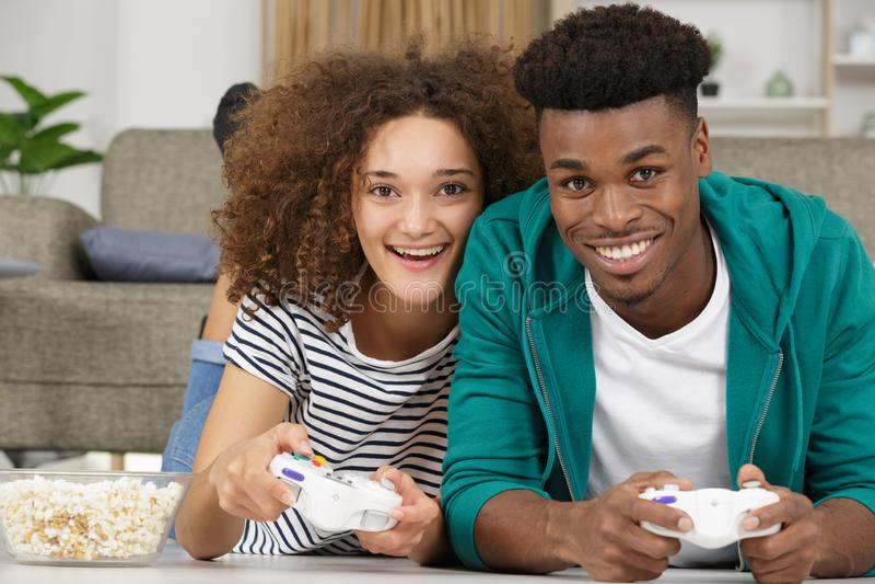 Pares felizes que encontram-se no assoalho ao jogar videogames fotos de stock royalty free