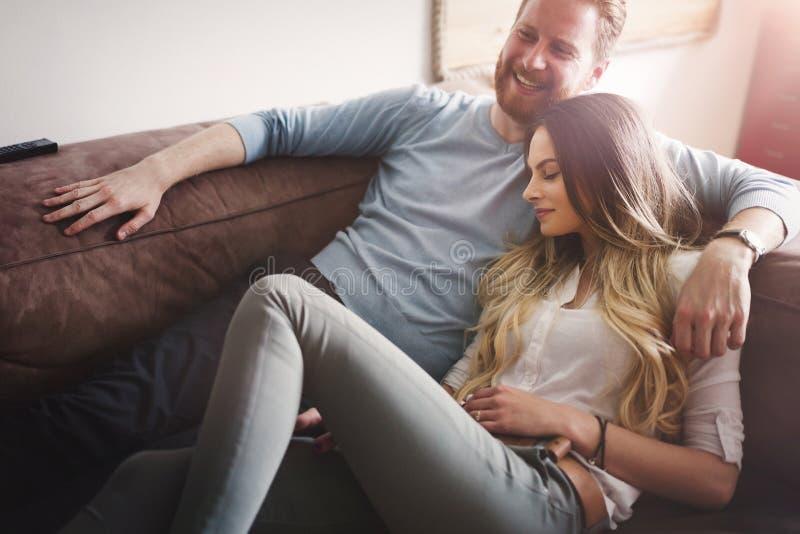 Pares felizes que encontram-se no sofá junto e que relaxam em casa imagens de stock