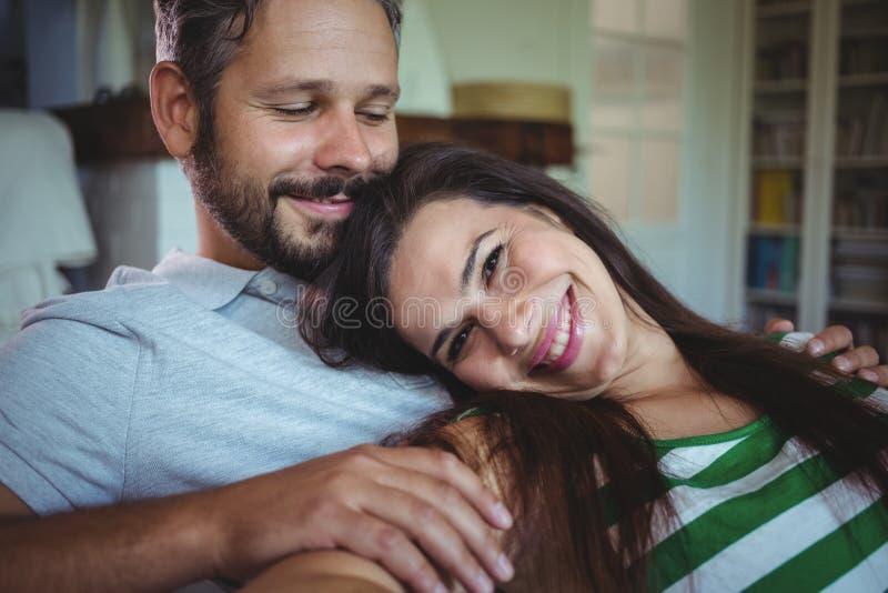 Pares felizes que encontram-se no sofá na sala de visitas fotografia de stock royalty free