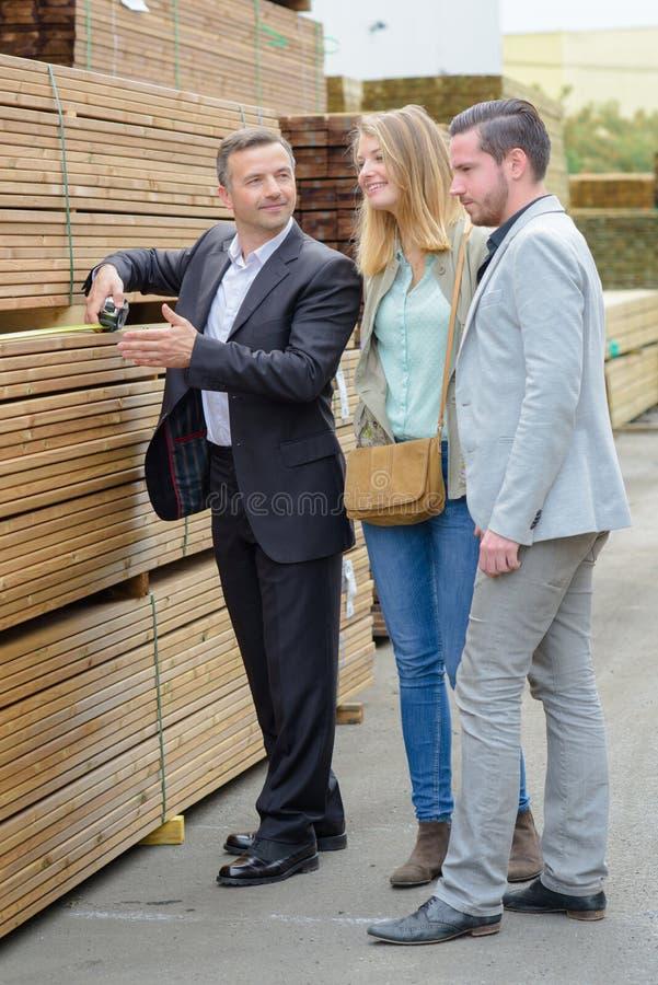 Pares felizes que escolhem a madeira para sua casa imagem de stock