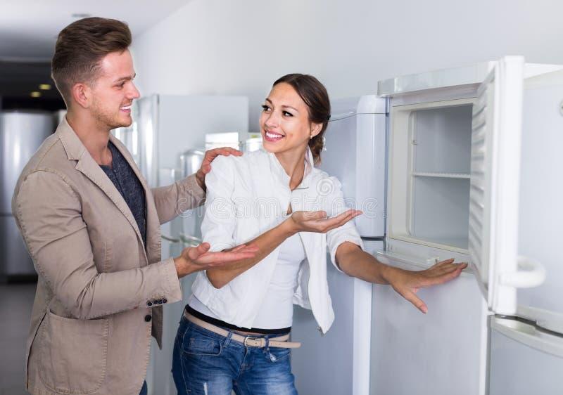 Pares felizes que escolhem o refrigerador novo no hipermercado foto de stock