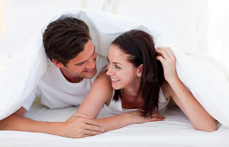 Pares felizes que falam em sua cama foto de stock royalty free