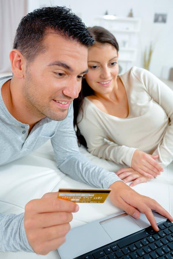 Pares felizes que fazem a compra em linha com cartão e portátil de crédito fotografia de stock royalty free