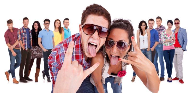 Pares felizes que fazem o gesto do rock and roll foto de stock royalty free